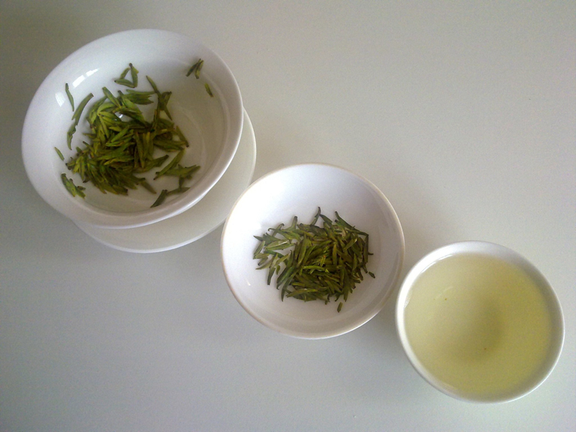 The appearance of green tea at three different stages (from left to right): the infused leaves, the dry leaves, and the liquor.  By Alessandro Martini (wikimedia)
